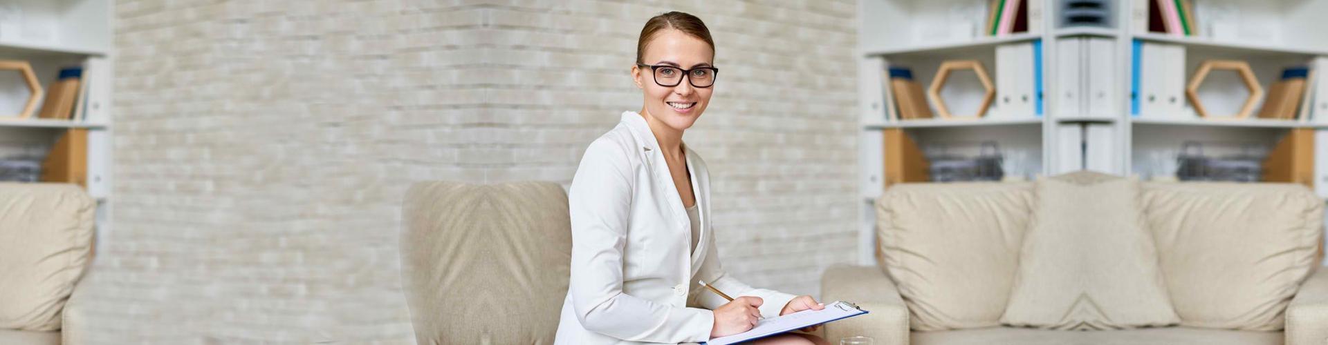 a pyschiatrist wearing glasses smiling
